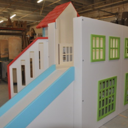 Custom playhouse with slide and green windowsills.