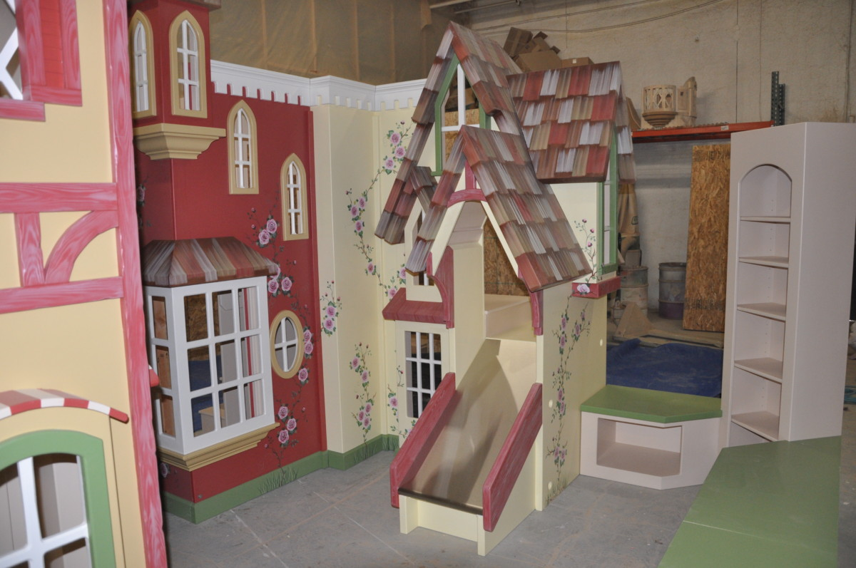 Indoor village playhouse with slide and stairs.