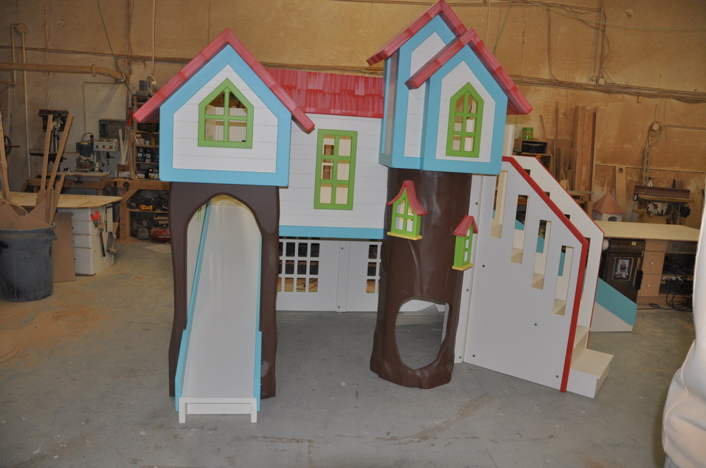 Custom playhouse with treehouse theme, two slides, stairs, and more.