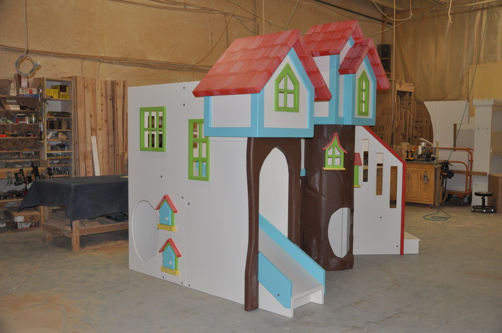 Custom playhouse with treehouse theme and two slides.