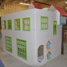 Custom playhouse with green windowsills and functional mailboxes.