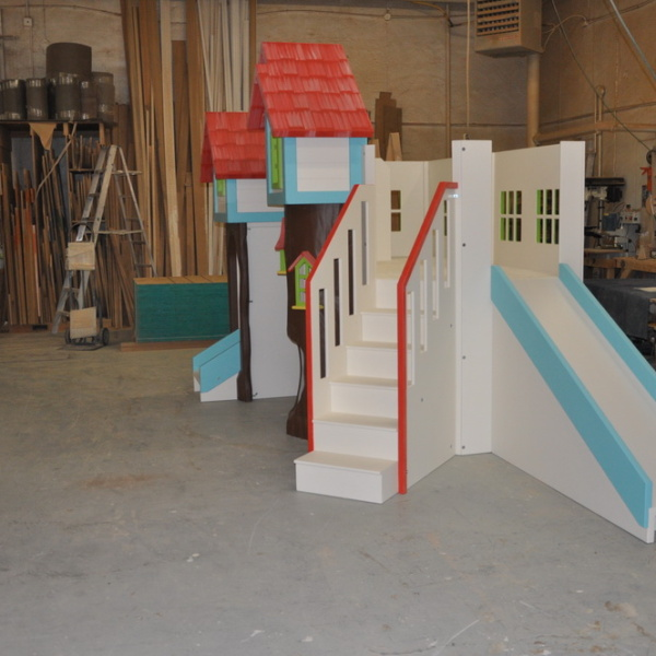 Custom playhouse with slide and stairs.