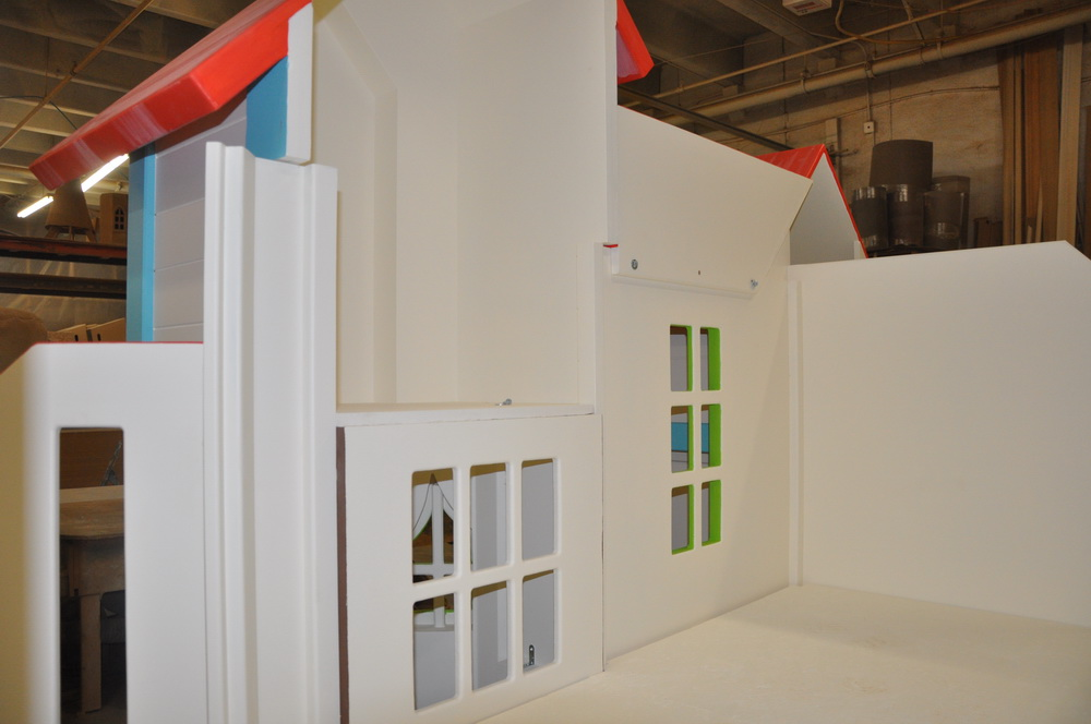Loft area of a custom indoor playhouse with slides.